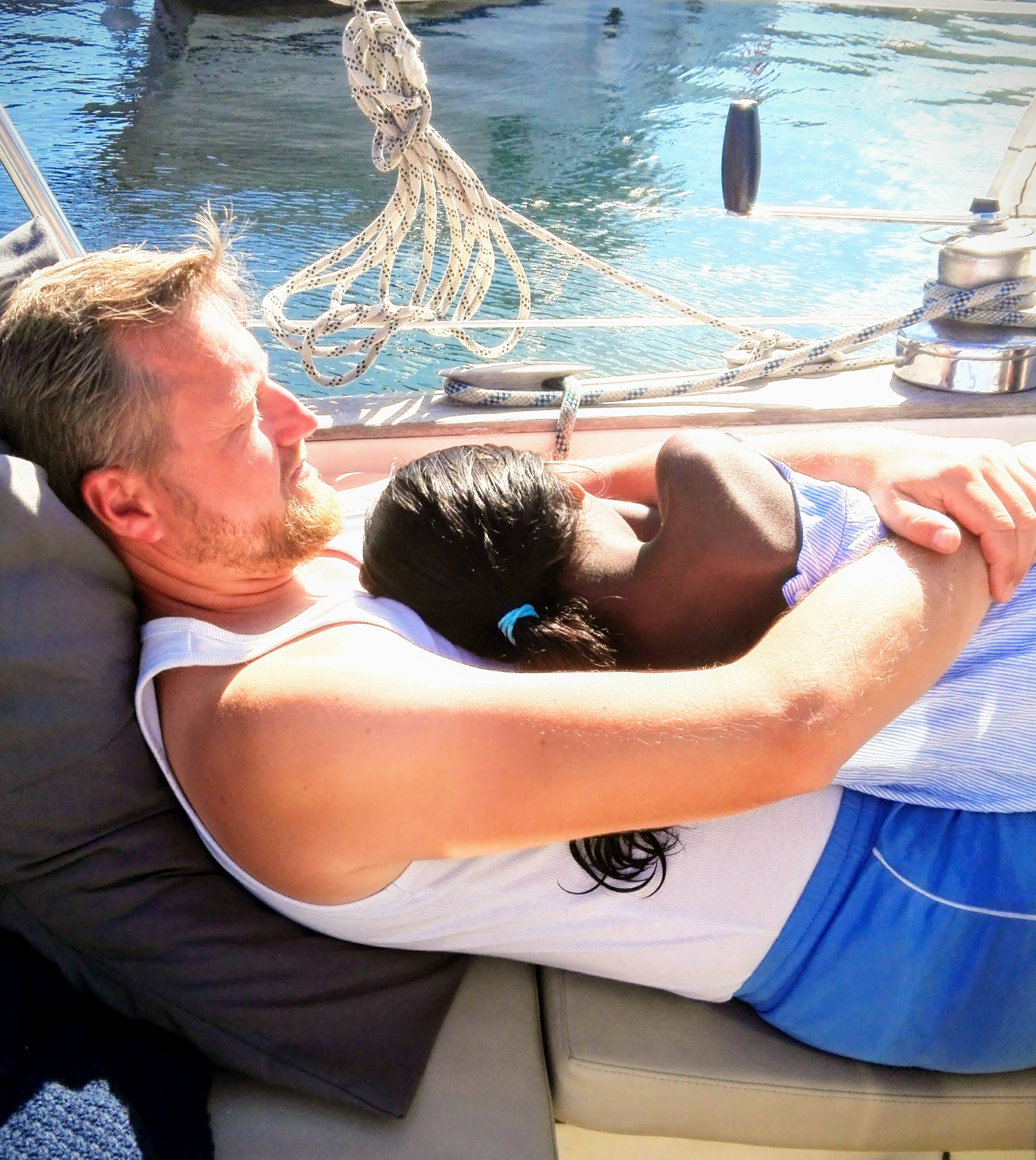 Man lying on a sailboat and holding his sleeping daughter in the arms