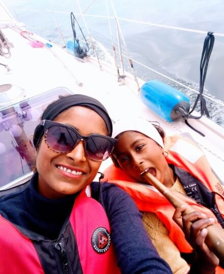 Mother and daughter smiling happily on a sailboat - Harba