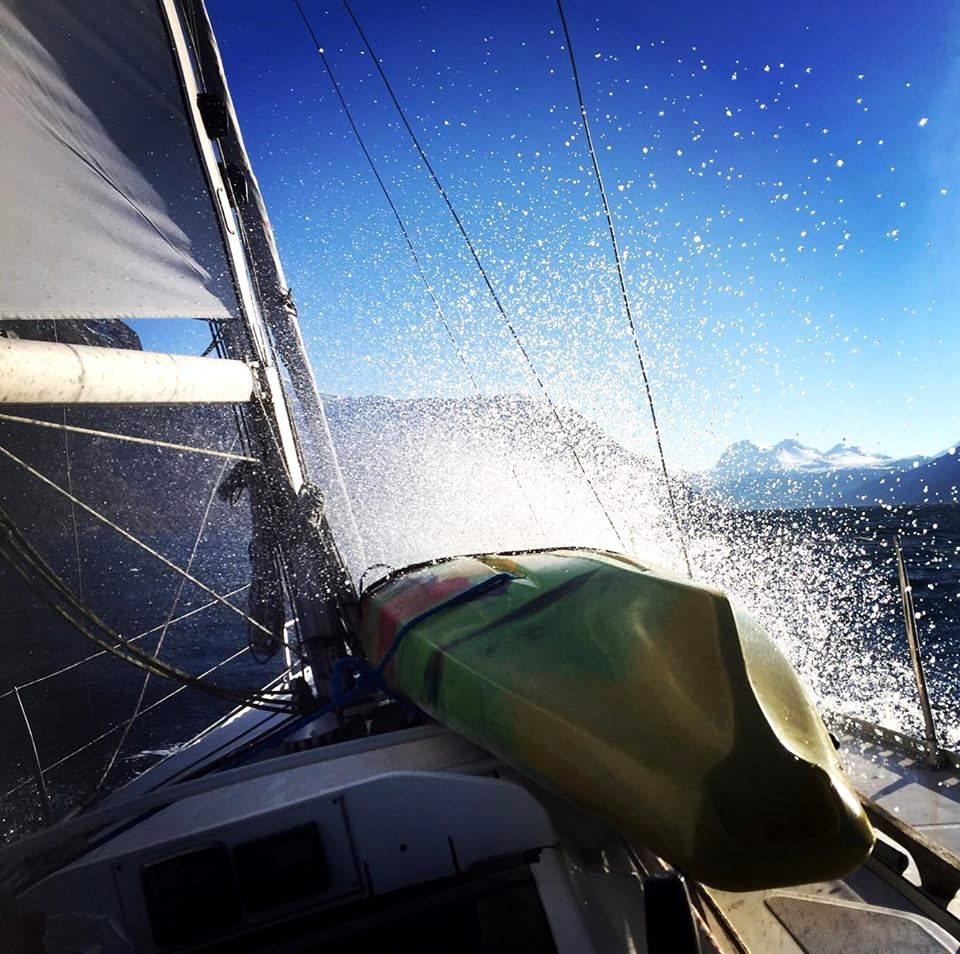 Sailboat's front with a huge splash of water shining in the sun
