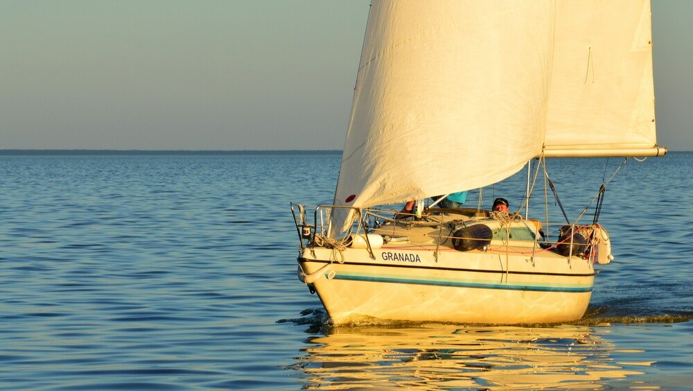 Sailor in his sailboat during the sunset in the Baltic Sea