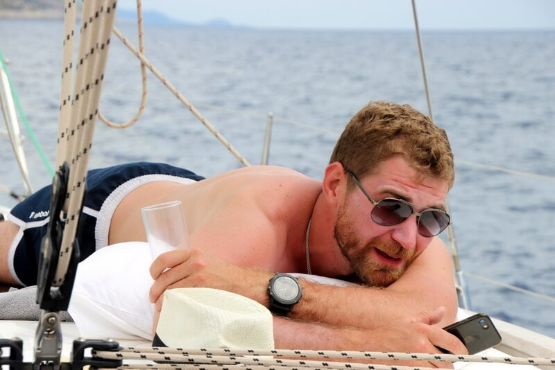 Man with sunglasses lying on a sailboat