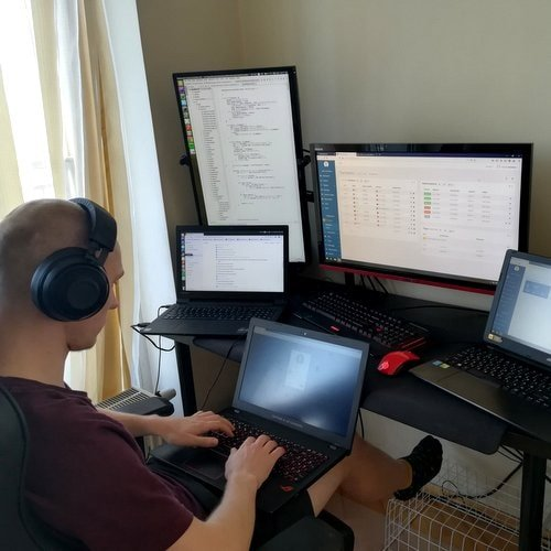 Man in front of five computer screens