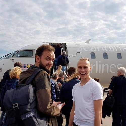 Two men next to the plane smiling before the trip