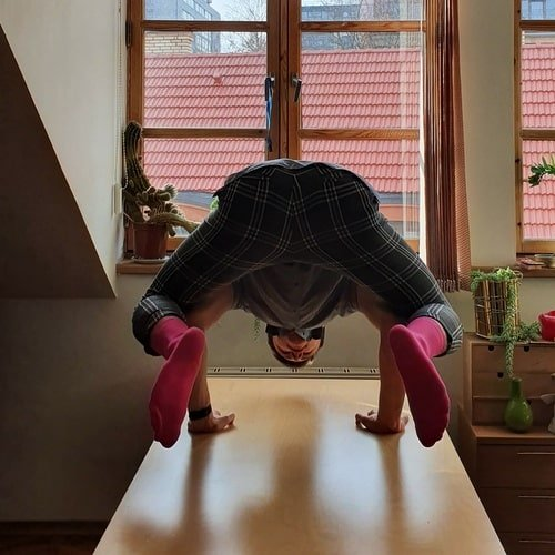 Man doing some yoga pose on a table