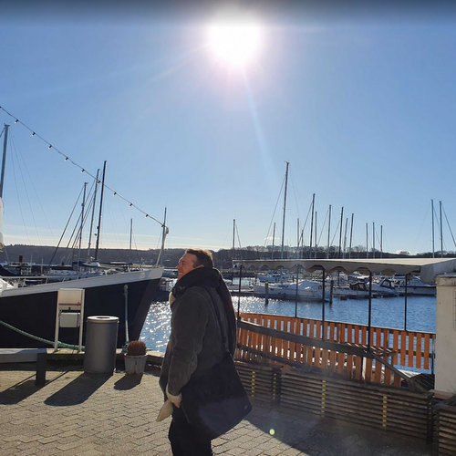 Man walking in a marina on a sunny day